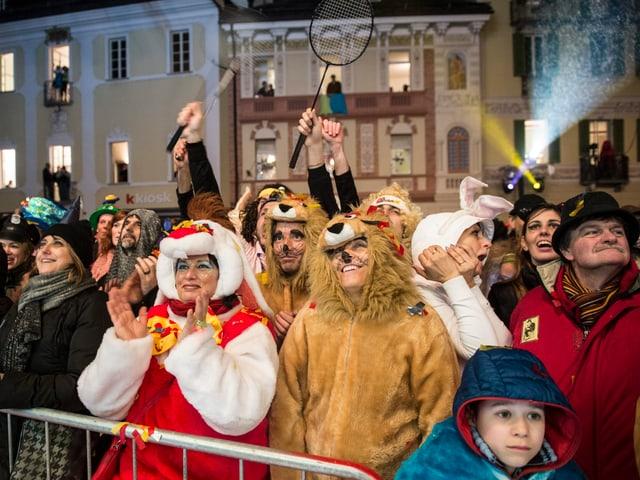 Kostümierte Besucher auf einem Platz in Dunkelheit, es wird Fasnacht gefeiert.