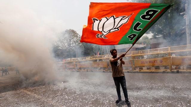 ein Mann mit einer Flagge, darauf steht gross BJP.