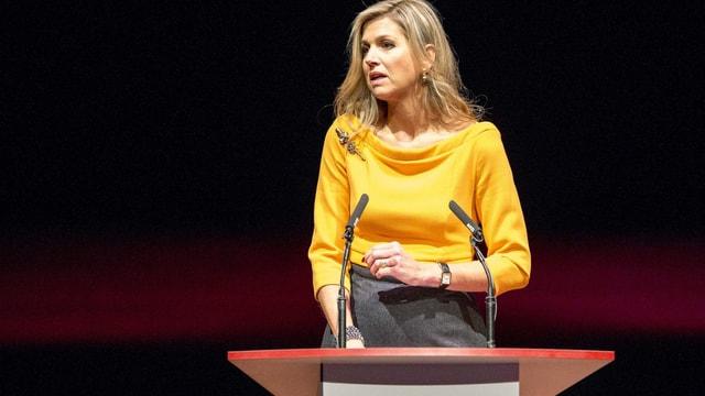 Königin Màxima in gelbem Oberteil am Rednerpult
