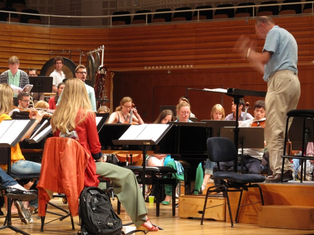 James Wood am Dirigentenpult, konzentrierte Musikerinnen und Musiker  der Festival Academy.