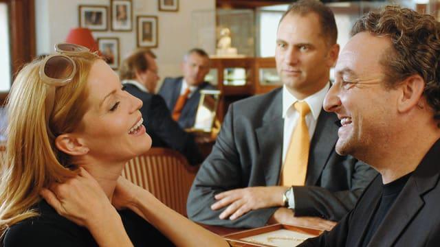 Eine Frau und ein Mann lachen sich liebevoll an. Ein Mann im Anzug sitz hinter den beiden am Tisch. Die Szene spielt sich in einem Restaurant ab.