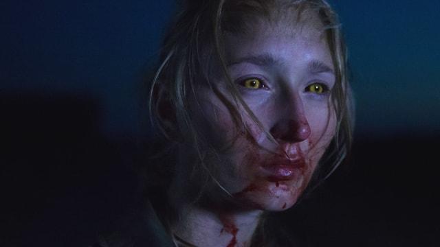 Man sieht eine junge Frau mit gelben Augen. Sie hat Blut im Gesicht.