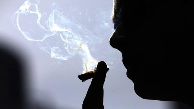 Gegenlichtaufnahme eines Mannes, der an einem Joint saugt.