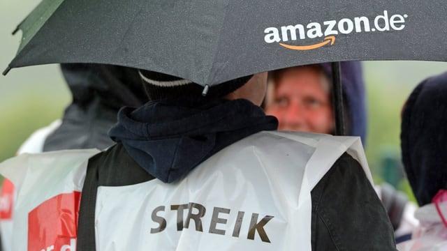 Eine Person trägt einen Regenschutz, auf dem das Wort Streik steht. In der Hand hält sie einen Regenschirm.