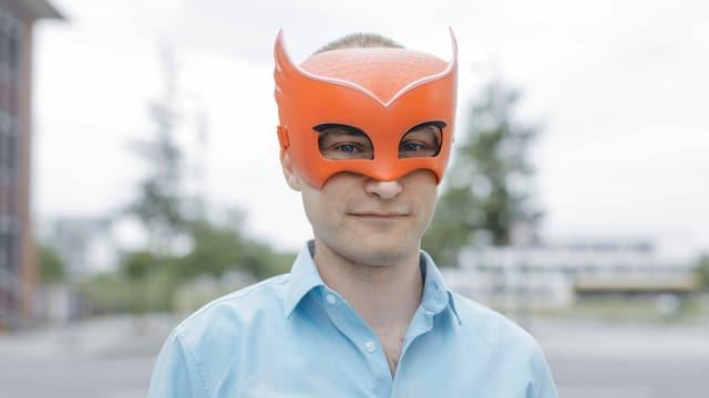 Ein Mann mit einer orangen Maske über den Augen.