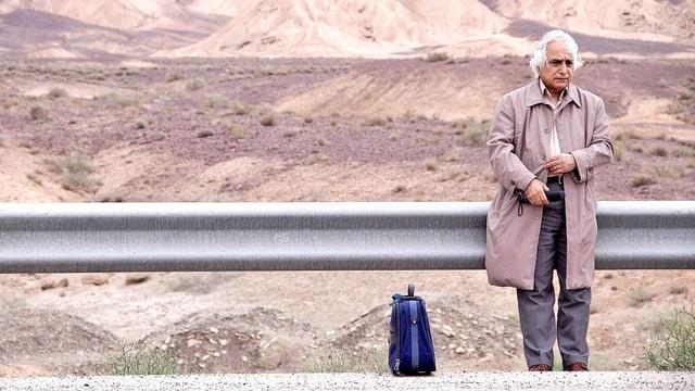 Am Rand einer Strasse in einer wüstenhaften Landschaft steht ein Mann, an die Leitplanke gelehnt.
