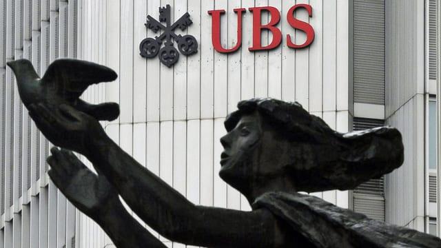 Der Schriftzug der Schweizer Grossbank UBS in Zürich. Im Vordergrund eine Frauenskulptur mit einer Taube. (keystone)