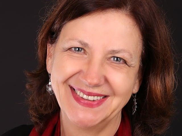 Karin Krieger trägt einen roten Schal und lächelt in die Kamera.