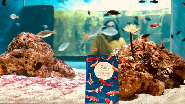 Das Buch «Die zehn Lieben von Nishino» von Hiromi Kawakami steht vor einem Aquarium, dahinter schwimmen Fische