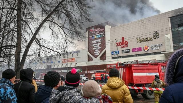Menschen stehen hinter einer Absperrung vor dem brennenden Einkaufscenter.