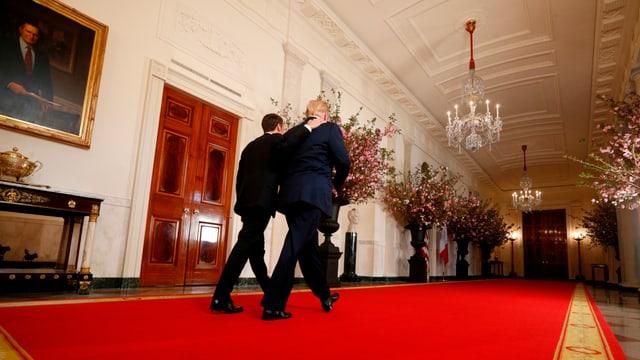 Macron und Trump von hinten, durch einen prunkvollen Flur im Weissen Haus schreitend. Macron umarmt Trump.