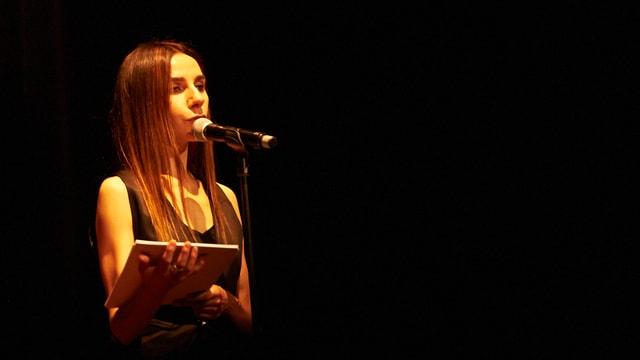 Frau auf einer Bühne vor einem Mikrofon. Sie hält einen Stapel Blätter in der Hand.