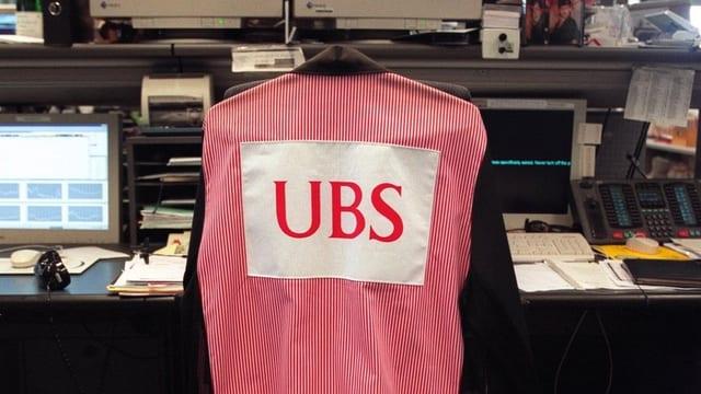 Über einem Stuhl häng eine Jacke mit der Aufschrift UBS. Der Stuhl gehört zu einem Arbeitsplatz in einer Bank.
