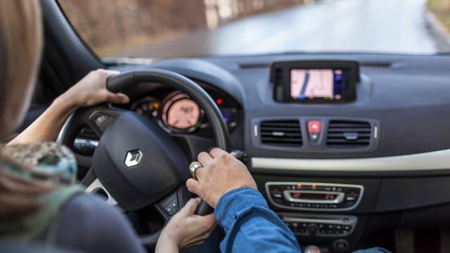 Fahrschülerin und Fahrlehrer im Auto.