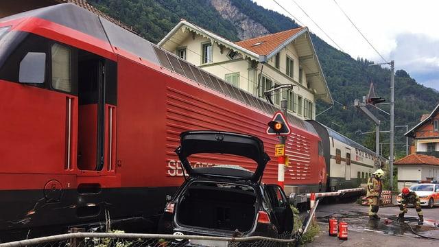 Stehen gebliebener Zug bei Bahnübergang, davor beschädigtes Auto