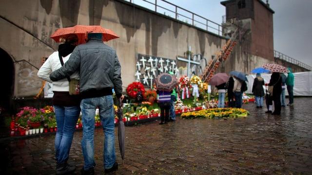 Menschen trauern beim Tunnelausgang in Duisburg, wo am 24. Juli 2010 21 Menschen starben.
