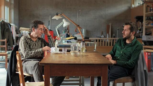 Eine Filmszene in der ein Vater und ein Sohn an einem Tisch sitzen und miteinander reden.