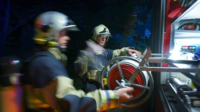 Zwei Feuerwehrmänner nehmen den Schlauch vom Wagen.