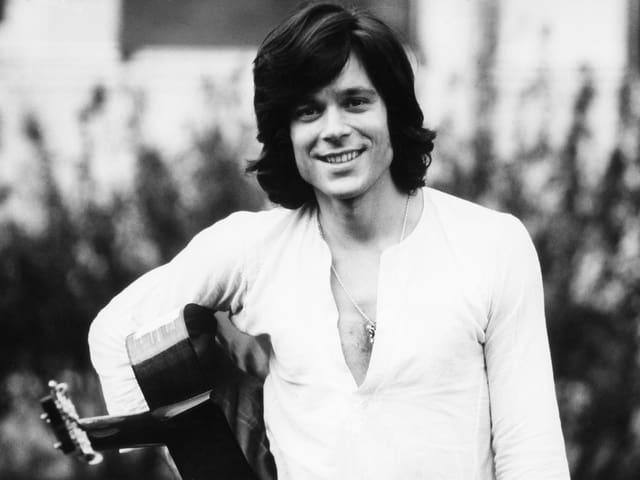Schwarz-weiss Bild des jungen Jürgen Drews. Er hat lange Haare, trägt ein weisses Hemd und in der Hand hält er eine Gitarre.