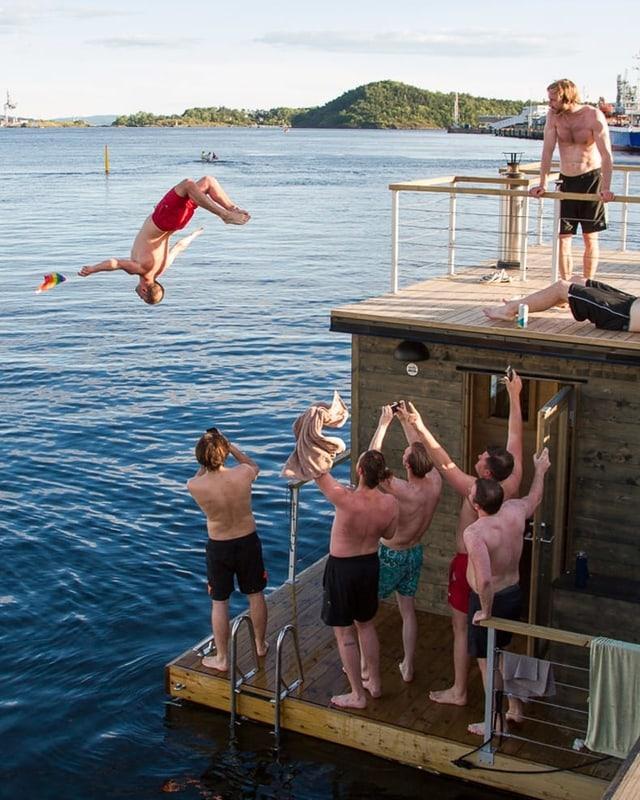 Ein Mann springt rückwärts von einem Hausboot ins Wasser. Seine Freunde jubeln ihm zu.
