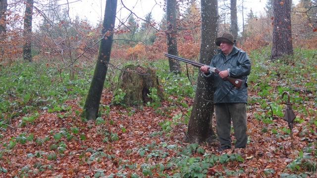 Mann mit Gewehr im Wald.