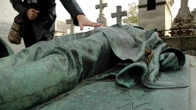 Ein Besucher fasst den Lendenbereich der Bronzestatue auf dem Grab des französischen Journalisten Victor Noir an.