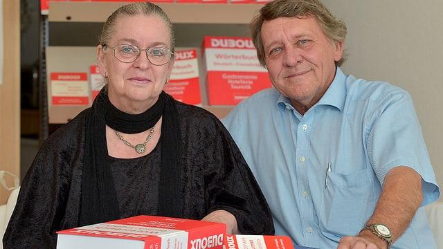 Ein Mann und eine Frau sitzen vor einem Wörterbuch.
