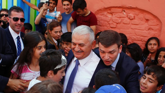 Binali Yildirim umgeben von Schülern und Sicherheitskräften in Istanbul.