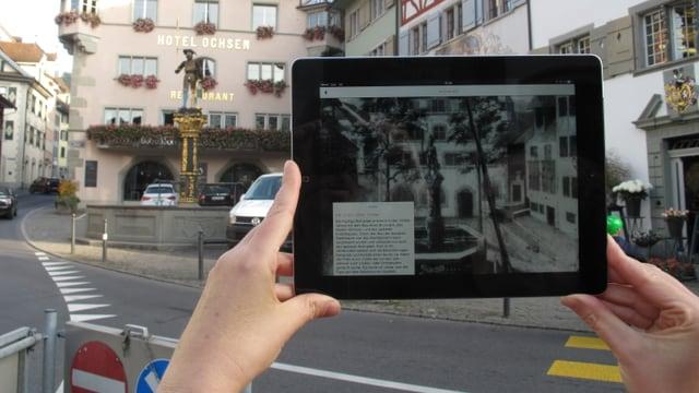 Bild des Brunnens auf dem Zuger Kolinplatz mit einer historischen Aufnahme auf dem App.
