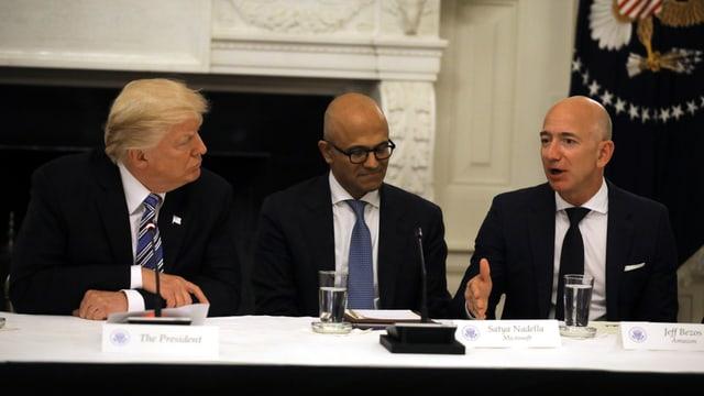 Trump, Nadella und Bezos sitzen nebeneinander.