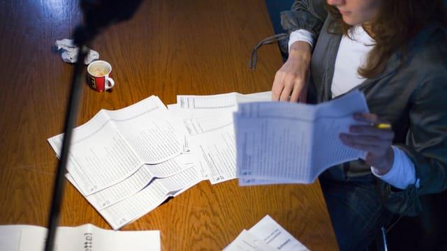 Eine junge Frau studiert die Wahlunterlagen.