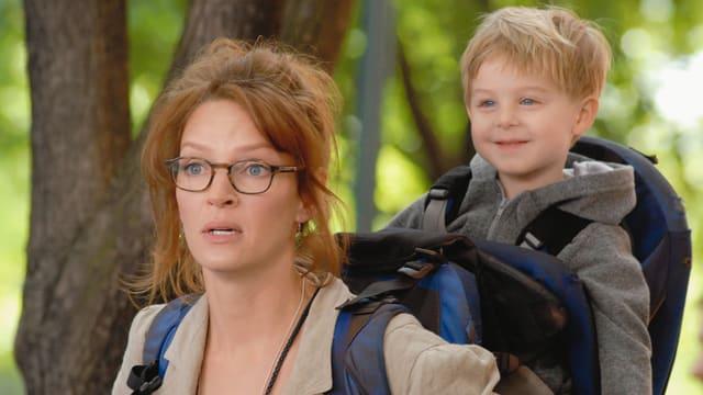 Eine Frau mit ihrem Sohn auf dem Rücken.