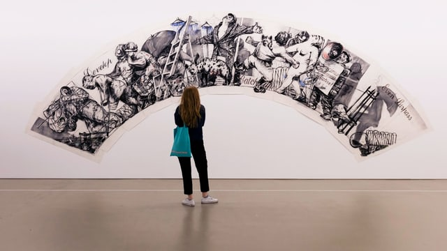 Eine junge Frau im Museum: sie steht vor Bildern, die wie ein Regenbogen angeordnet sind.