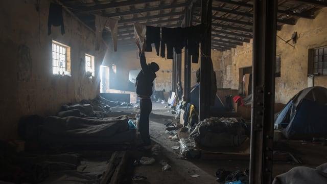 Schlafplätze am Boden einer dreckigen, verlassenen Baracke. Man sieht Männer, die in Decken eingewickelt schlafen, Zelte und viel Abfall. Ein Mann hängt Wäsche auf.