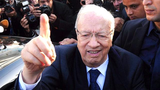 Der designierte tunesische Präsident Béji Caïd Essebsi steigt aus einem Auto und hebt den Zeigefinger.