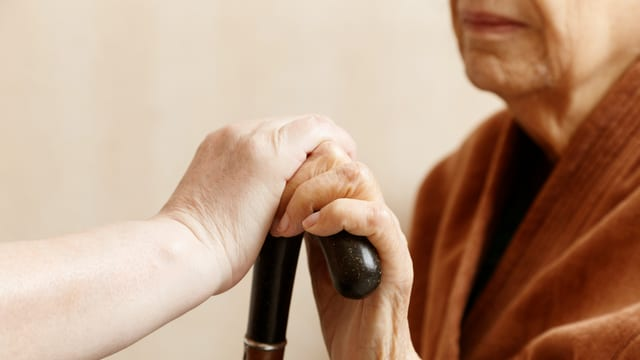 Eine Frau hät mit einer Hand einen Stock. Eine andere Person hält die Hand und den Stock.
