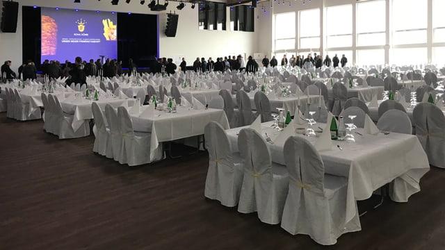 Ein Saal mit weiss gedeckten Tischen, im Hintergrund Menschen vor einer Leinwand