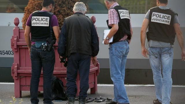 Französische Polizisten stehen auf einer Plattform und schauen sich Beweismaterial an