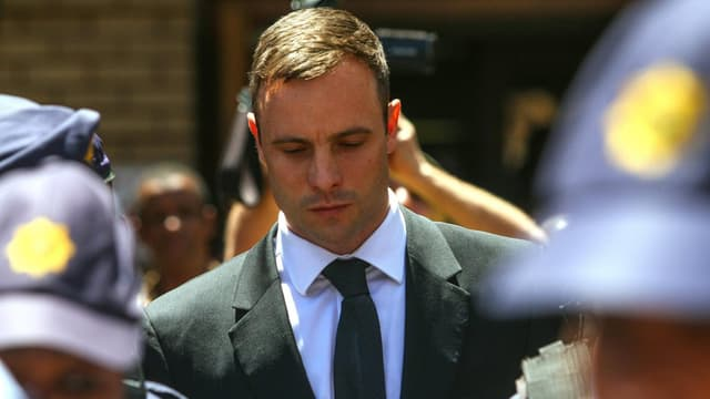 Pistorius, in Anzug und Trauerkrawatte, geht umgeben von Polizisten zum Gerichtsgebäude