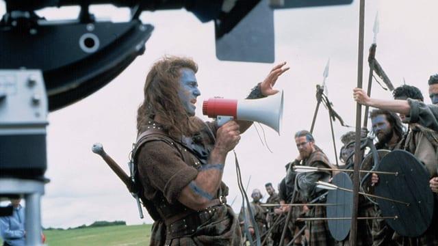 Ein Mann mit langen Haaren, Schottenrock und einem Megafon in der Hand steht vor einer Horde verkleideter Männer und gibt Anweisungen.