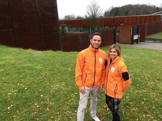 Adrian Küpfer und Sabine Dahinden stehen auf der Wiese vor dem Sammlungszentrum des Schweizerischen Nationalmuseums in Affoltern am Albis.