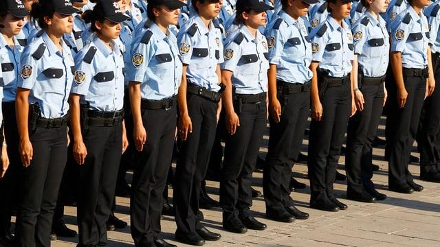Purtret d'ina colona da policists tircs che fan parada.