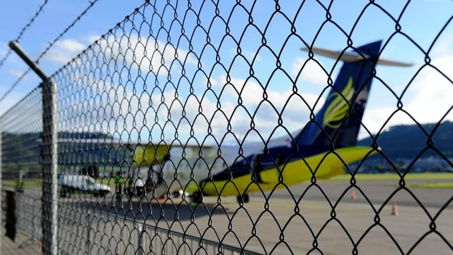 Ein unscharfes Flugzeug der Skywork hinter einem Zaun.