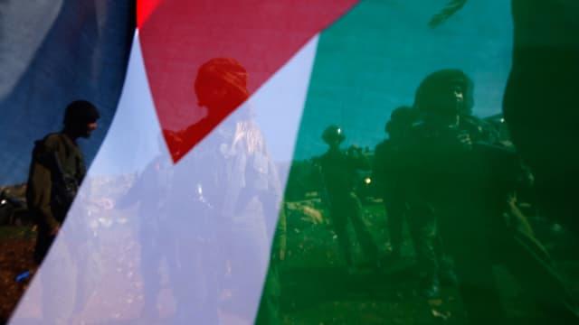 Israelische Soldaten, aufgenommen durch eine Palästinenser-Flagge.