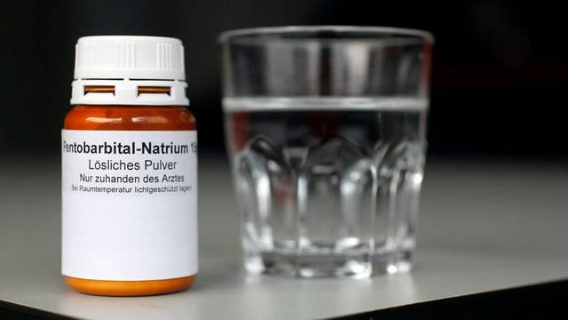 Wasserglass und Medikamentenfläschchen