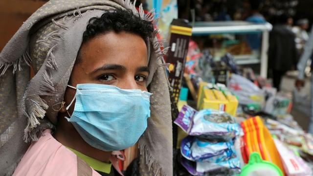 Verkäufer mit Maske an seinem Stand.