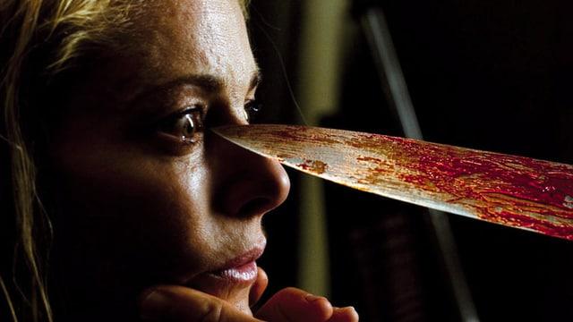 Eine Frau hält sich ein Messer ans Auge.