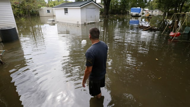 Mann mit Stiefeln in überschwemmter Landschaft