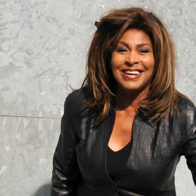 Tina Turner posiert strahlend ganz in schwarz gekleidet mit Lederjacke.