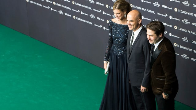 Eine Dame im Abendkleid und zwei Männer in schwarzem Anzug auf einem grünen Teppich